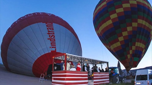 Grounded hot air balloons boarding people.