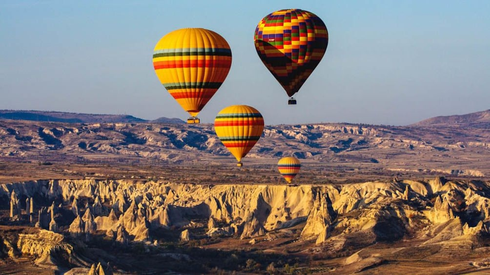 Show item 1 of 5. Hot air balloons floating over canyons.