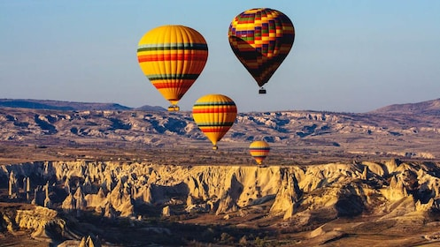 Hot air balloons floating over canyons.