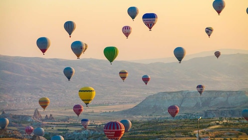 Several hot air balloons floating over canyons.