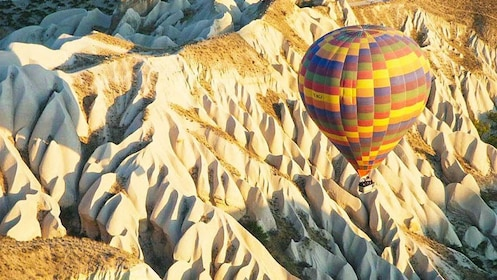 Hot air balloon floating over canyon.