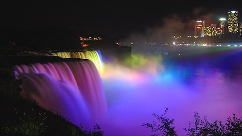 Niagara Falls illuminated at night.