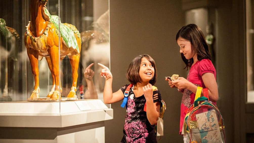 Two children observing displayed art at museum.