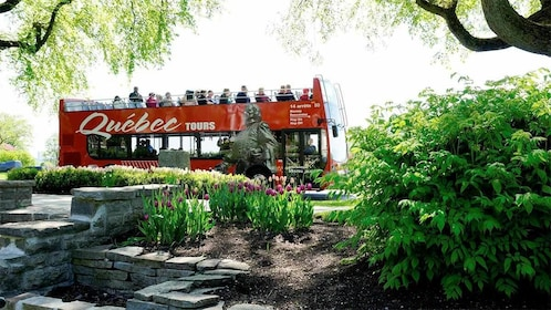 Le Bus Rouge Hop on Hop Off bus tour in front of a beautiful garden in Quebec