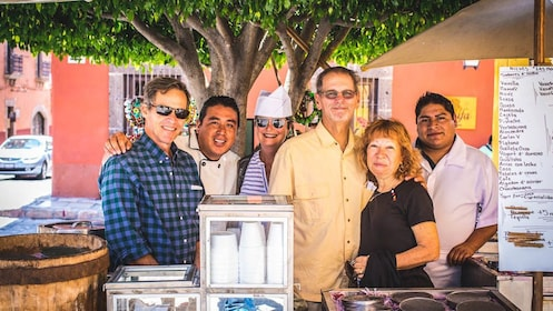 Group of tourists posing with cooks at food stand.