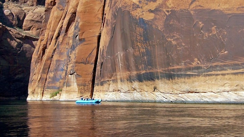 raft floating by magnificent rock cliffs in Colorado