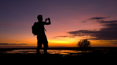 Silhouette of a man taking a photo of a sunset