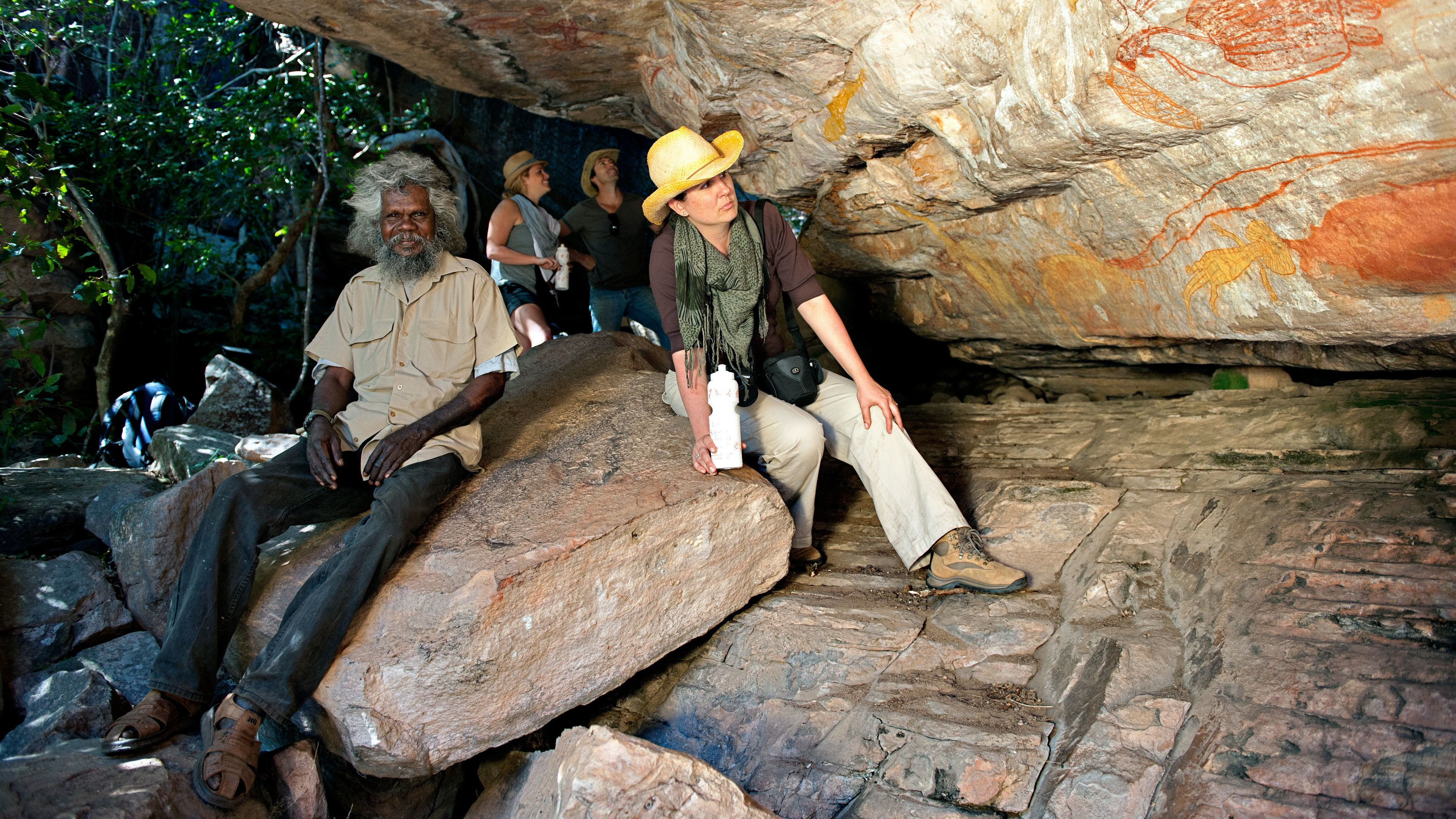 Tour group looking at rocks with ancient drawings