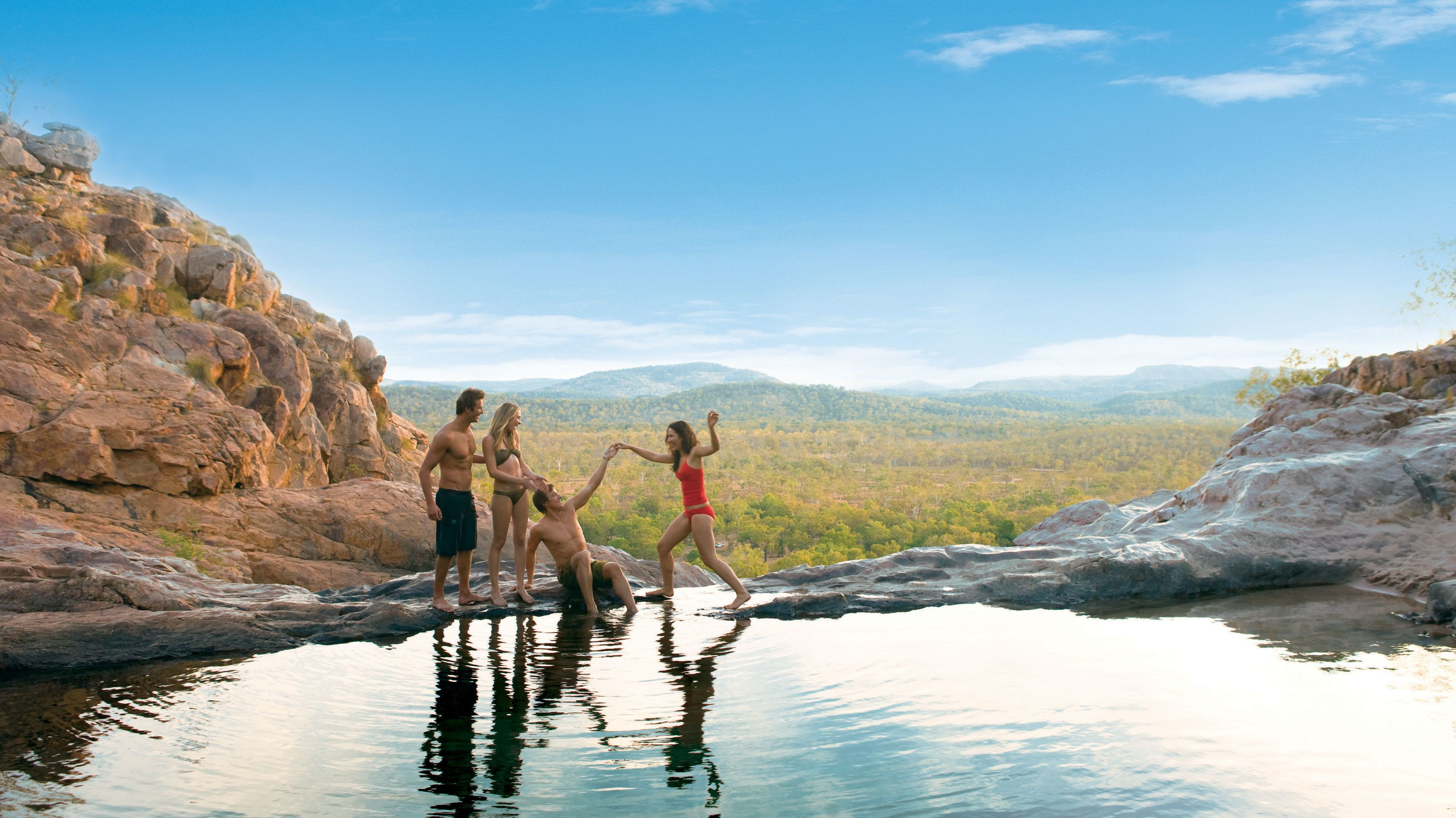 Group on the edge of a natural pool with mountains in the background