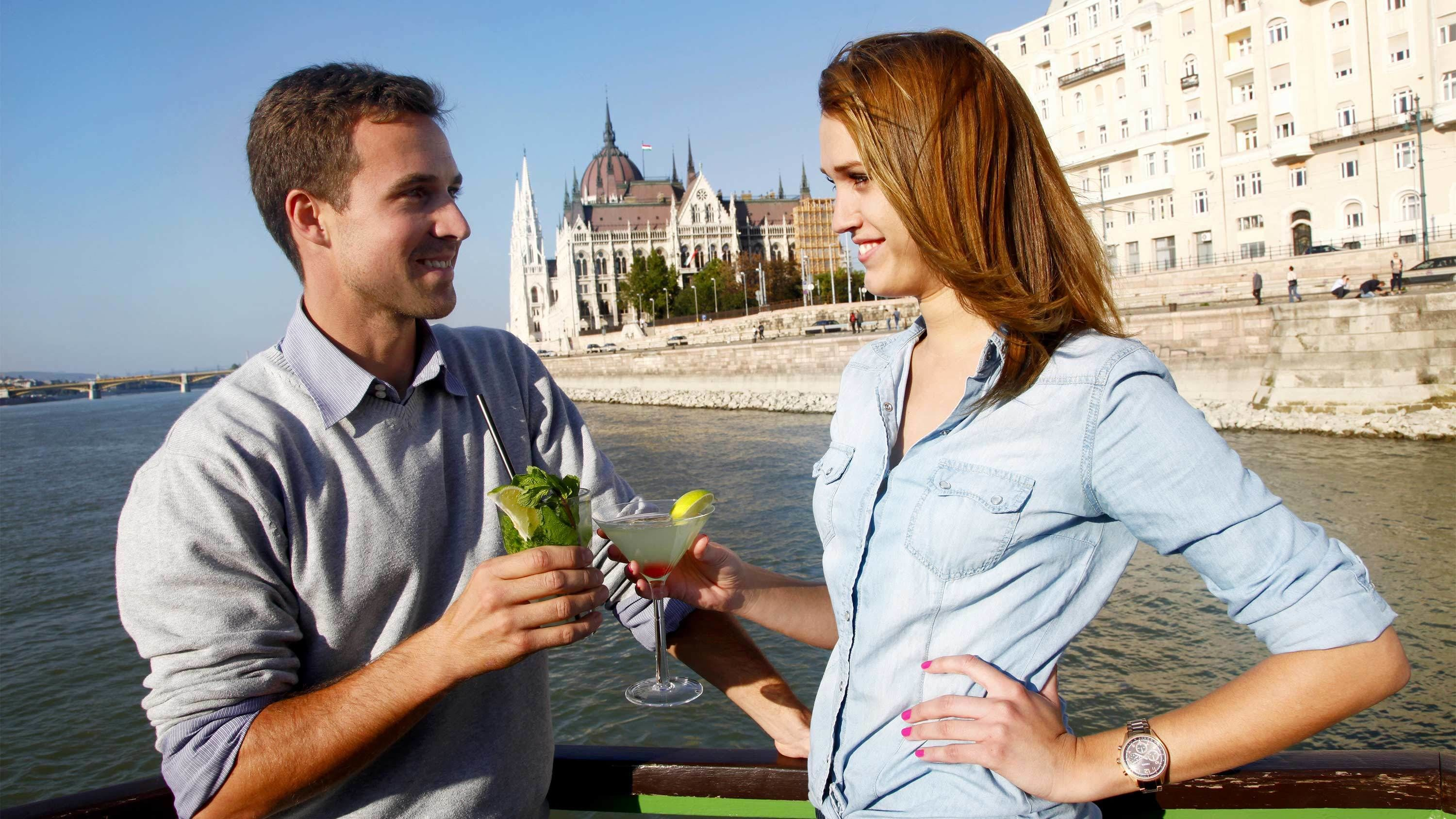 Couple enjoying a cruise with drinks in Budapest