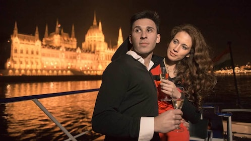 Couple enjoying their drinks aboard the cruise at night in Budapest