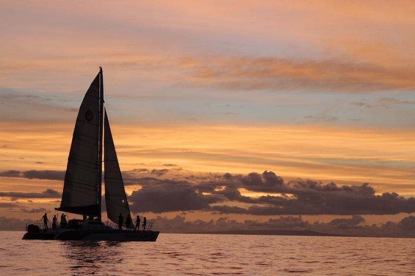 Show item 1 of 7. People standing out on catamaran as is sails smoothly at dusk off of Maui