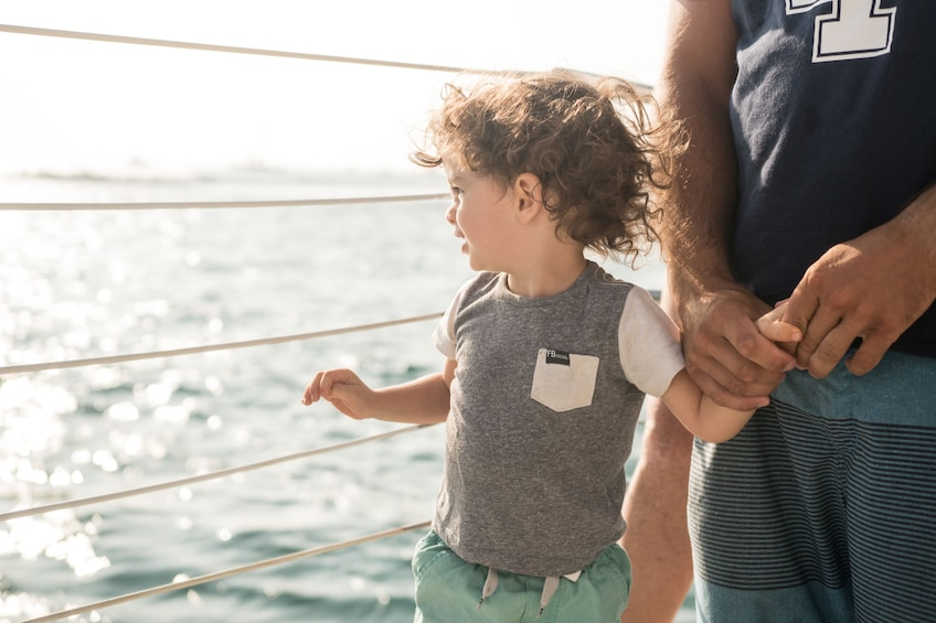 Show item 3 of 7. Young boy holds father's hand on catamaran off of Maui