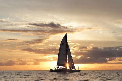 Catamaran sailing past sunset off of Maui