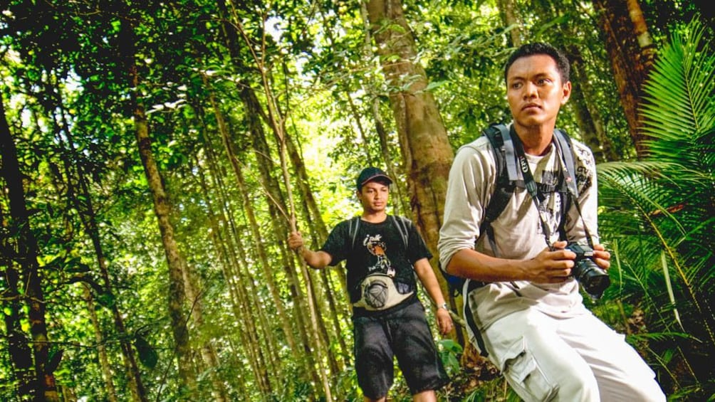 Show item 1 of 5. Two men hiking through forest.