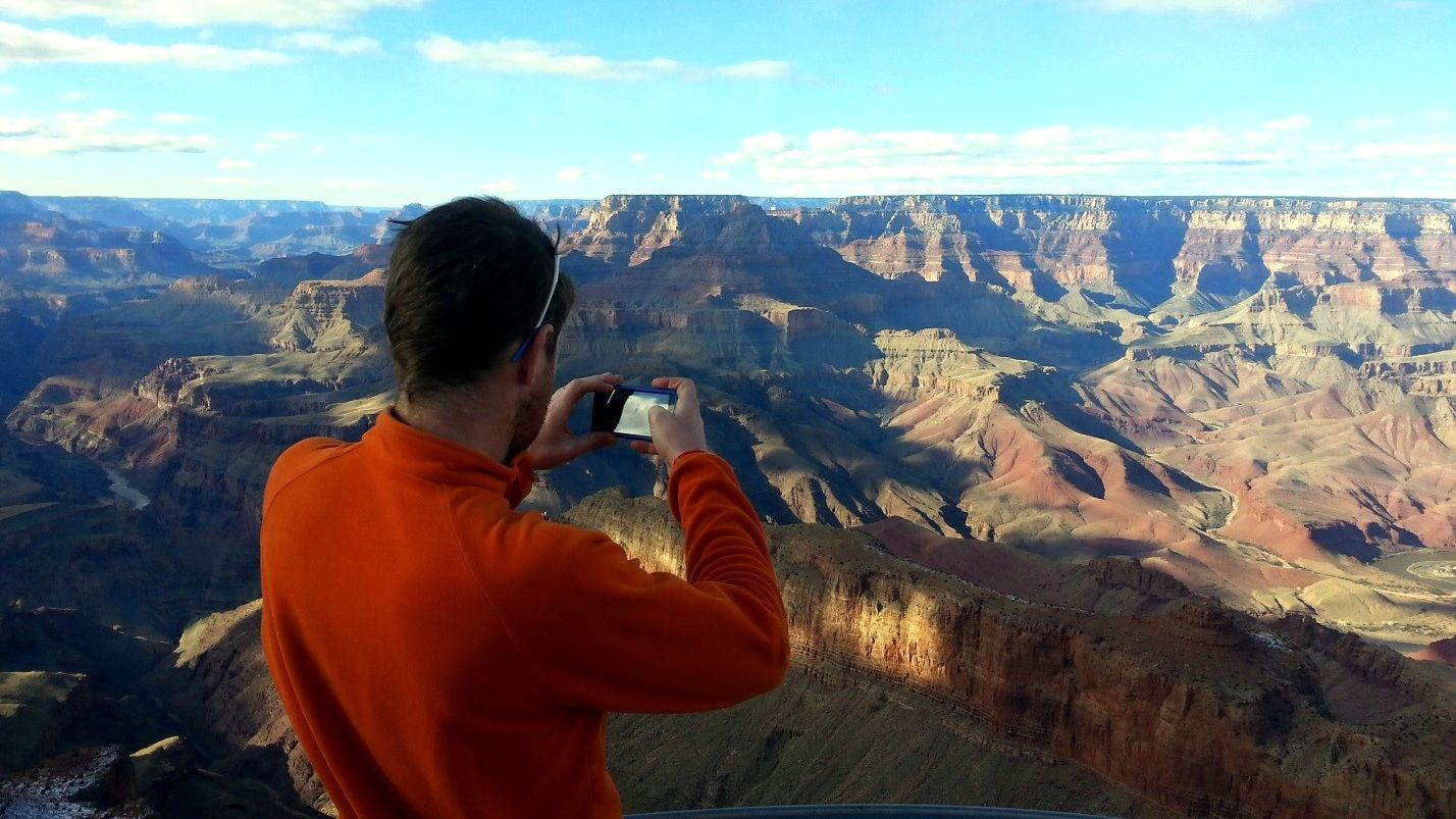 Man takes a picture of the Grand Canyon