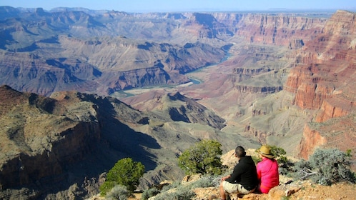 Two people sit and look at the Grand Canyon