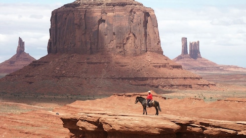 A cowboy on a horse on a cliff in monument park