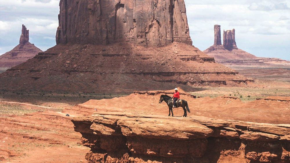 Landscape view of Monument Valley with tourist seen on horse.
