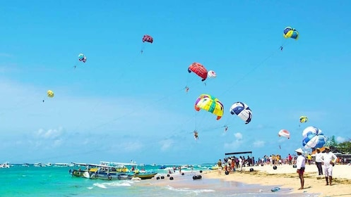 scattered parasailers in the sky at the beach in Bali
