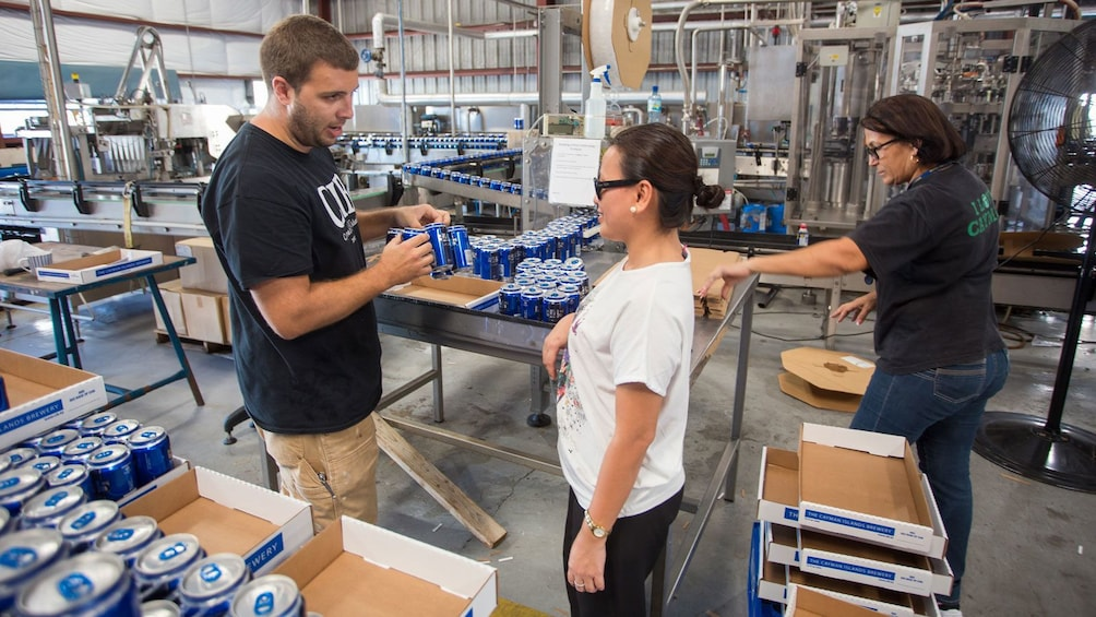 Guide talks to woman in beer canning facility in Cayman Islands