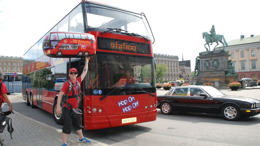 Lataa valokuva 10 kautta 10. Tour guide standing in front of a hop on hop off bus in Stockholm