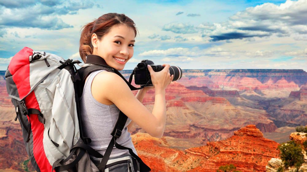 Smiling woman taking photo of beautiful Grand Canyon landscape.