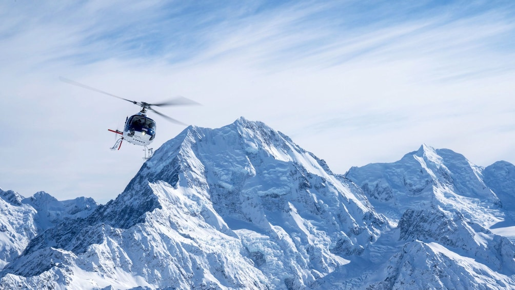 Show item 5 of 5. Helicopter flying with Mount Cook in background in New Zealand