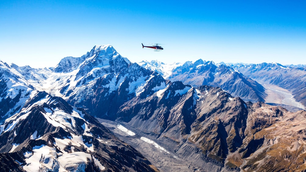 Show item 1 of 5. Helicopter flying high past Mount Cook in New Zealand
