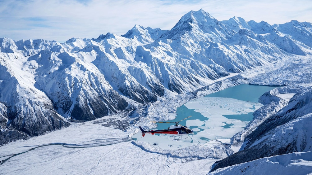 Show item 3 of 5. Helicopter hovers over glacier at base of Mount Cook in New Zealand