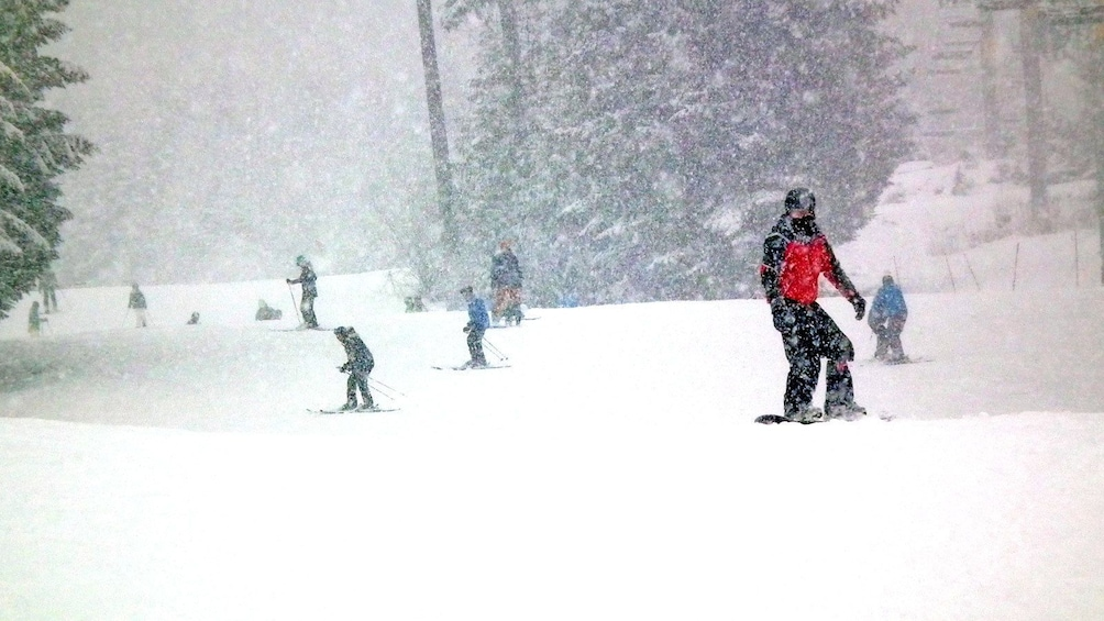 Show item 4 of 4. snowboarding during heavy snowfall in Whistler