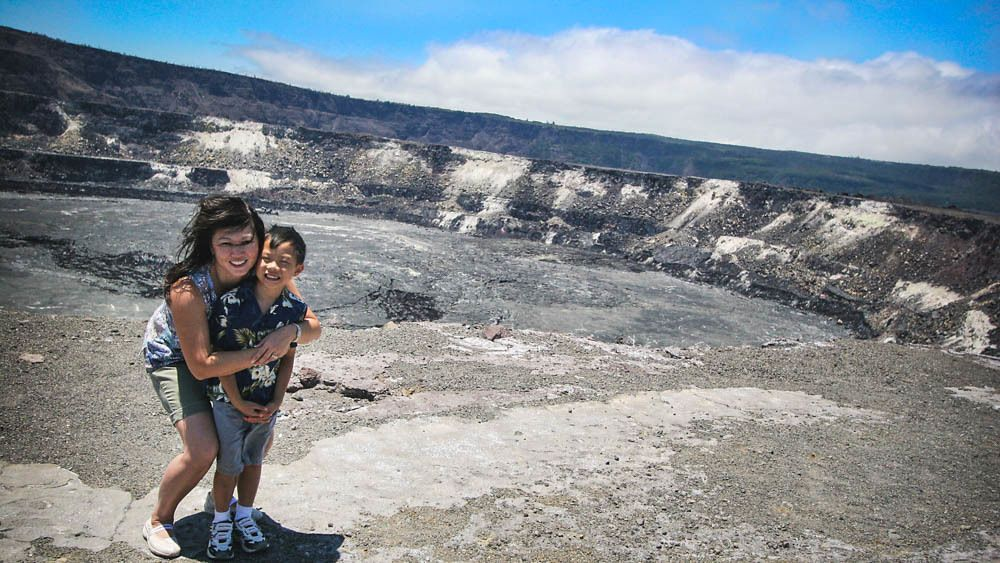 Mother and son posing near volcano center.