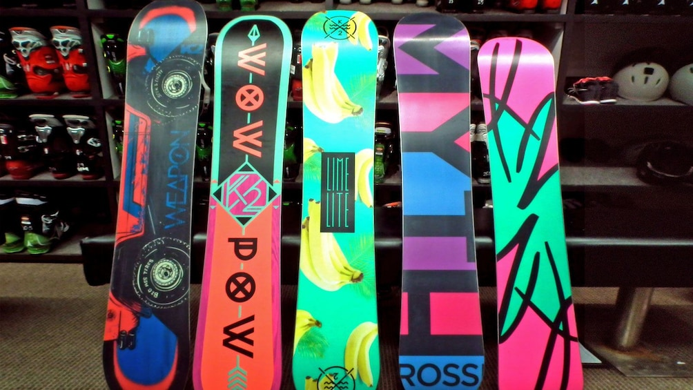 Show item 2 of 6. vibrant colored snowboards leaning on a bench at the rental in Whistler