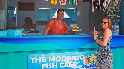 Woman getting a plate of food in the Cook Islands