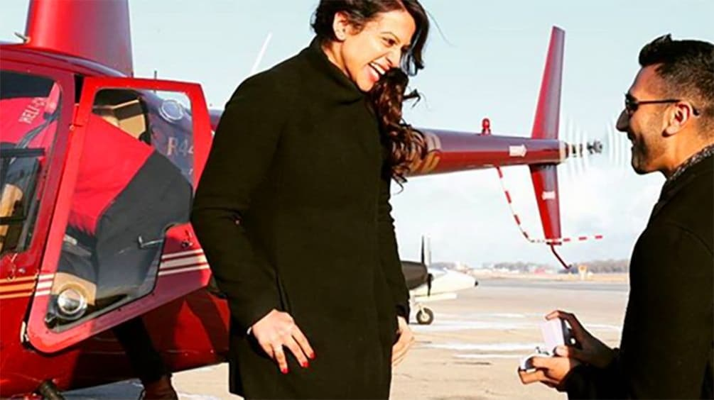 Man proposes to woman next to a Helicopter