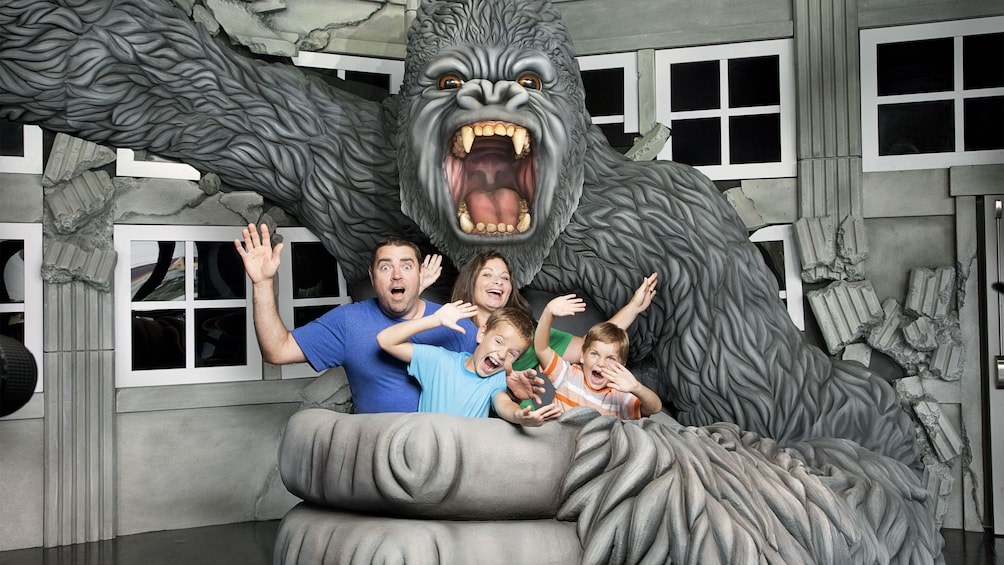 Show item 4 of 4. Family taking a photo with a fake gorilla at the Hollywood Wax Museum Entertainment Center in Myrtle Beach, South Carolina