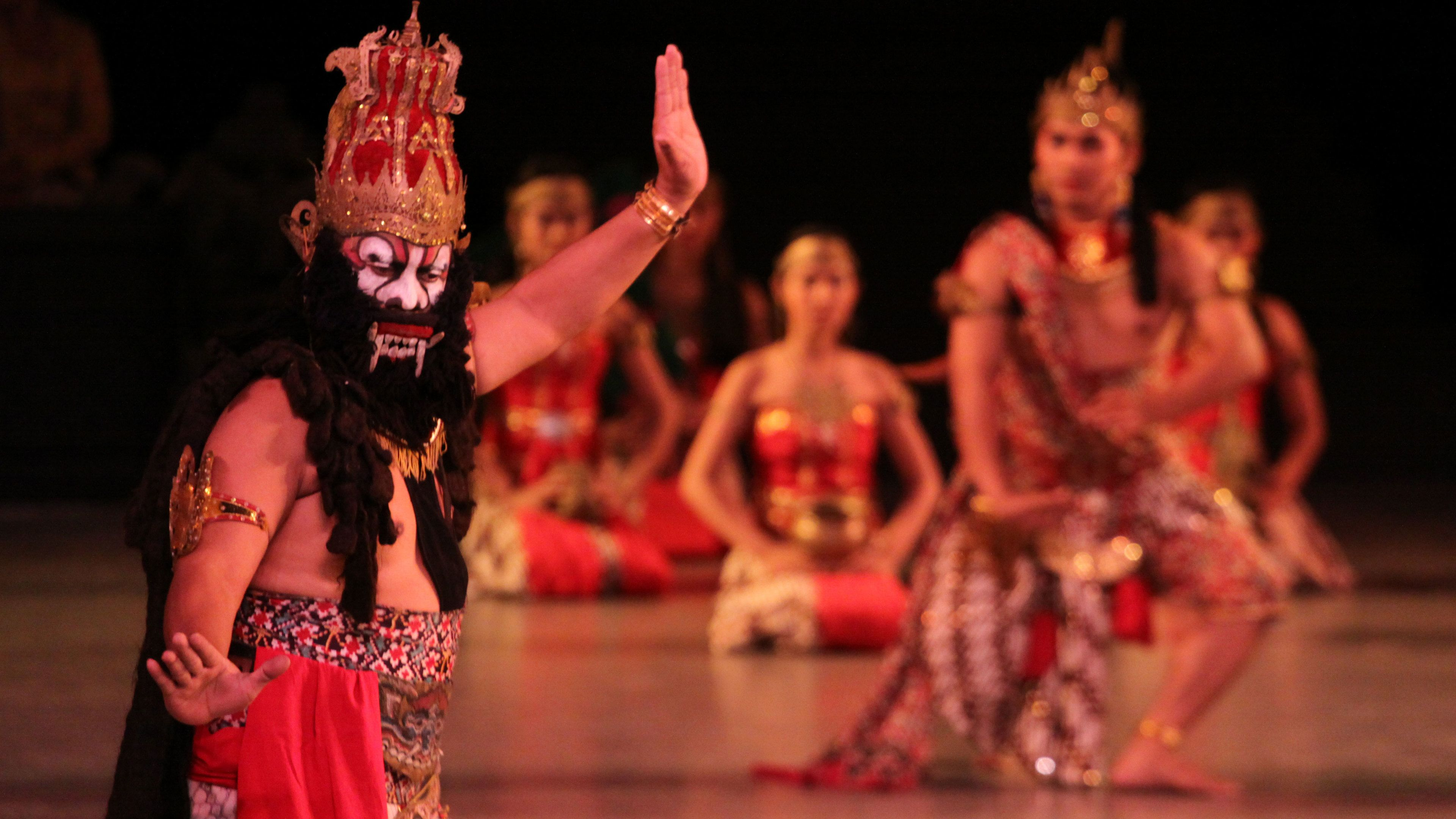 Man in a mask with dancers in the background onstage in Bali
