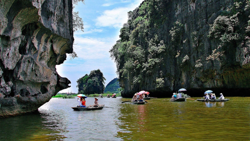 Show item 4 of 5. Boats floating down Tam Coc, Vietnam