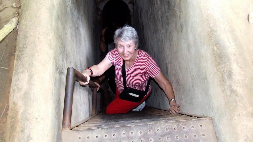正在顯示第 5 張相片,共 10 張。 Woman climbing out of the Cu Chi Tunnel in Vietnam