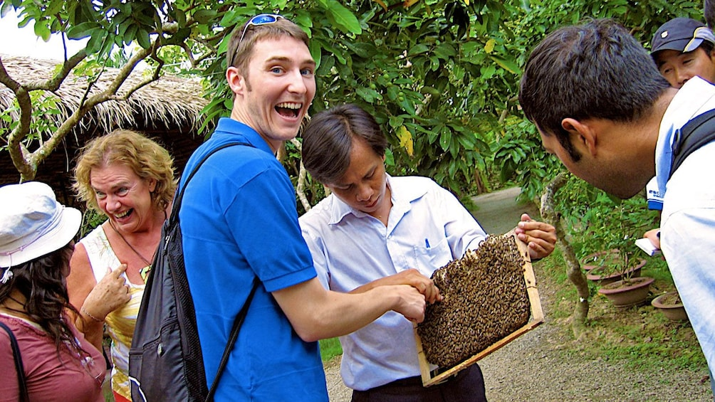 正在顯示第 5 張相片,共 10 張。 visitors interacting with a sectioned bee hive in Vietnam