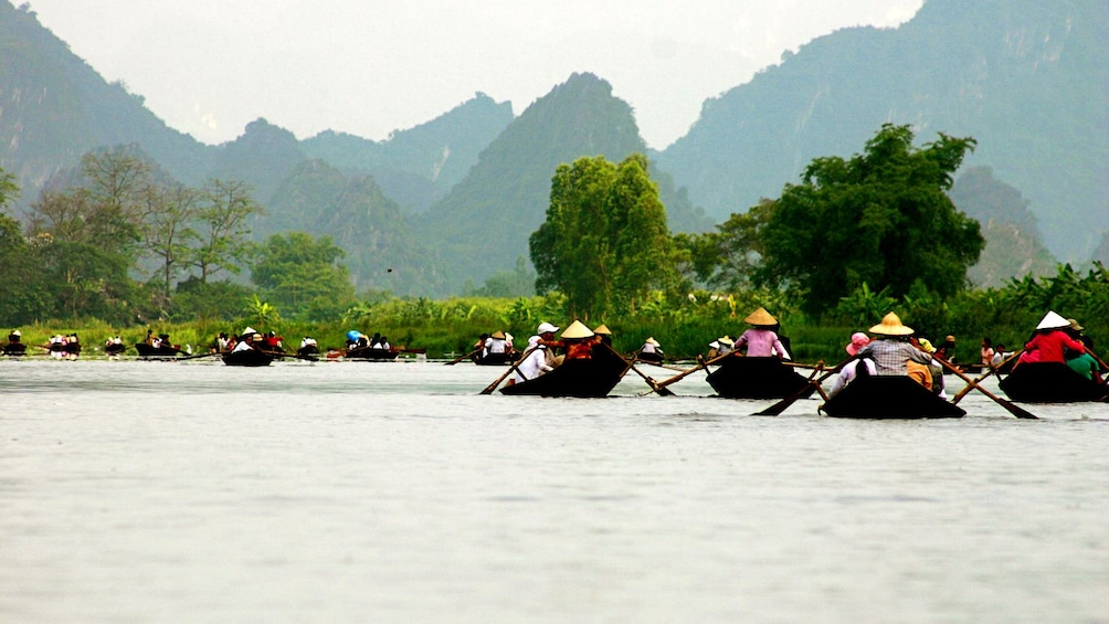 Tour boats on the perfume river in Vietnam with hills in the background