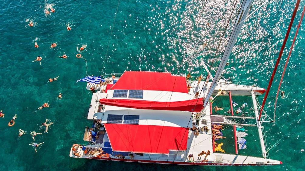 Show item 3 of 9. Aerial view people swimming around the catamaran off of Santorini, Greece