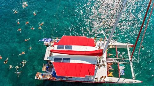 Aerial view people swimming around the catamaran off of Santorini, Greece