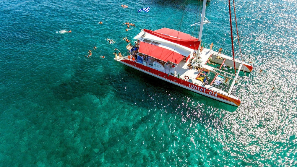 Show item 2 of 9. Aerial view people swimming around the catamaran off of Santorini, Greece