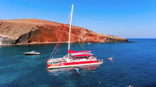 People swimming around the catamaran off of Santorini, Greece