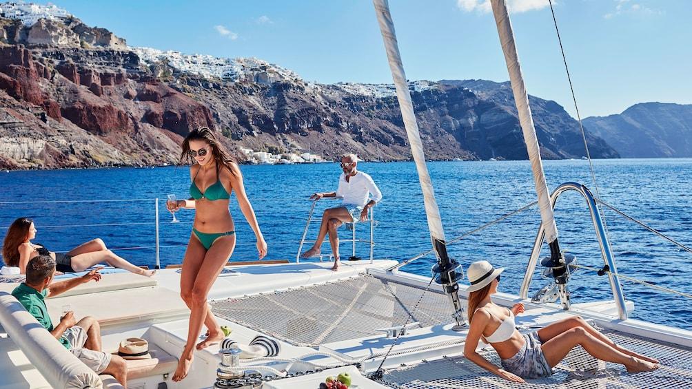Show item 2 of 8. People enjoying the sun on catamaran in Santorini