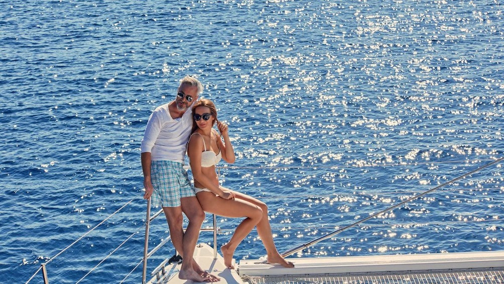 Show item 8 of 8. Couple standing by railing on catamaran in Santorini