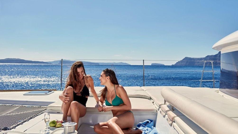 Show item 3 of 8. Woman enjoying food and drinks on Catamaran in Santorini