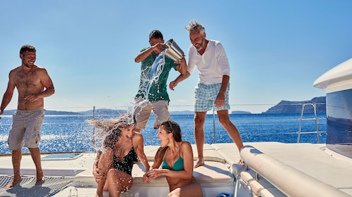 Guys pouring water on women on catamaran in Santorini