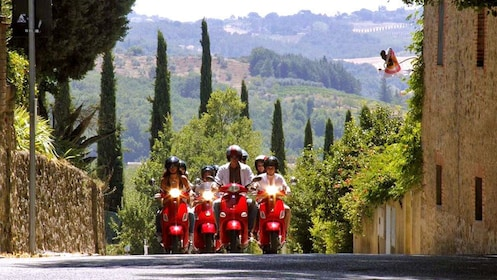 group riding Vespas around the town in Italy